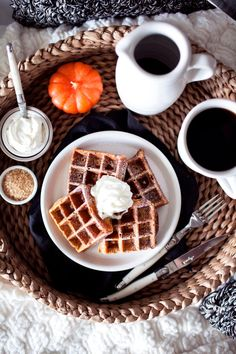 Waffles on white plate with black napkin on basket tray with coffee and pumpkin candle