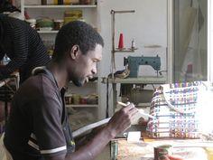 Djibi aux finitions du sac VIBRATION dans l'atelier de Keur Massar, Dakar, Sénégal
