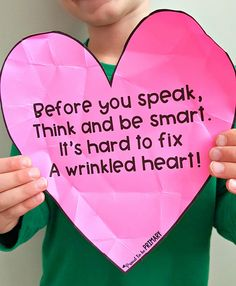 A child holding up the wrinkled heart poem on a heart cut out for an empathy classroom activity. Teach kids about empathy, compassion, inclusion, and community. #empathy #emapthybooks #socialemotionallearning #charactereducation #booksforkids #videosforkids #empathyactivities #socialskills #socialresponsibility