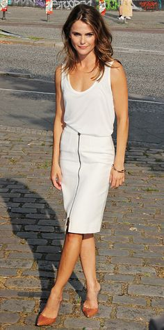 At the Dawn of the Planet of the Apes photo call in Berlin, Keri Russell elevated a basic tank by The Row with a zippered white Belstaff pencil skirt and caramel-PVC Gianvito Rossi pumps.