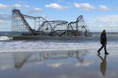 John Okeefe walks on the beach as a rollercoaster that once sat on the Funtown Pier in Seaside Heights, N.J., rests in the ocean on Wednesday, Oct. 31, 2012 after the pier was washed away by superstorm Sandy which made landfall Monday evening. (AP Photo/Julio Cortez)