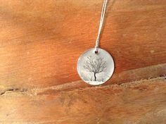 """Sterling Litho """"Fruit Tree"""" Necklace  An image a fruit tree is printed onto a 7/8"""" sterling silver disc then protected with a smooth layer of clear resin and hung from an 18"""" gray nylon thread cord with sterling silver o-ring clasp."""