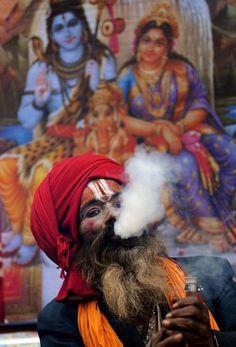 Sadhu smokes ganja in chilum, as holy offering to Lord Shiva