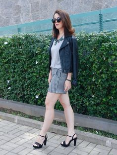 Look short de cintura alta pied poule com blusa cinza, casaco de couro e maxi colar com salto