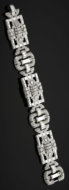 An Art Deco white gold and diamond bracelet, English, circa 1930. The six rectangular and oval links lavishly mounted in white gold with step and brilliant cut diamonds.