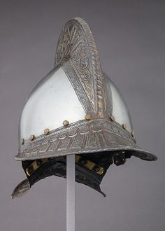 Burgonet    Date:ca. 1550  Culture:French  Medium:Steel, gold, leather, brass  Dimensions:H. 12 in. (30.5 cm); W. 8 7/16 in. (21.4 cm); D. 15 1/8 in. (38.4 cm); Wt. 3 lb. 14 oz. (1757 g)  Classification:Helmets  Credit Line:Gift of William H. Riggs, 1913  Accession Number:14.25.606