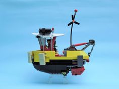 A tugboat inspired by the world of Ian McQue. There is a spring loaded engine that allows the chain in the back to be automatically re-winded.