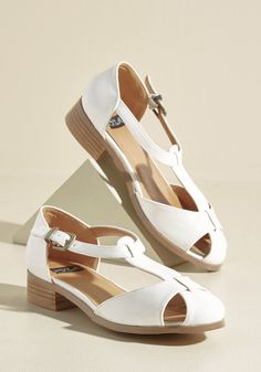 <p>What's your secret to a perfectly put-together look? These ModCloth-exclusive flats, of course! Keeping this pair on the hush-hush is no easy task, though, because the glossy faux-leather uppers and stacked heels of these white T-straps were simply made to be flaunted!</p>