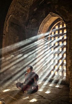 Photograph Sunrays on monk through window of Stupa by Spencer Tan on 500px