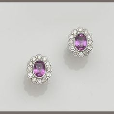 A pair of pink sapphire and diamond oval cluster earstuds Estimate: £700 - 800 US$ 1,100 - 1,300 €870 - 990  © Bonhams 2001-2012
