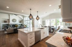 Amazing kitchen features a pair of black cage lanterns placed above a white center island topped ...