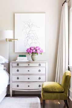Classic bedroom styling with an antique white dresser as nightstand, pink peonies, and an olive green velvet slipper chair.