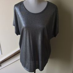 Vince Camuto Silver Top Features: Short sleeve shimmery silver material with round neck and round hem.  Measures 28 inches from shoulder.  Worn once in excellent condition. Size M. Two by Vince Camuto Tops