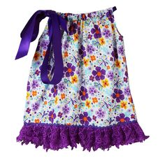 A cute pillowcase dress by Dress Up Dreams Boutique will make your girl look fabulous and feel comfy on hot summer days. The dress features a purple and blue floral pattern with lace trim and a rick-rack accent. It has a satin drawstring ribbon that ties