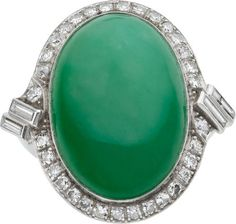 Art Deco Jadeite Jade, Diamond, Platinum Ring The ring features an oval-shaped jadeite jade cabochon measuring 23.57 x 16.26 x 9.46 mm and weighing approximately 34.90 carats, enhanced by European, single and baguette-cut diamonds weighing a total of approximately 1.00 carat, set in platinum.