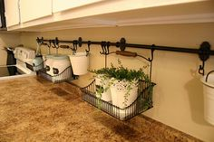 Keeping the clutter off the counter - love this idea. Can use a shower rod and curtain hooks if necessary