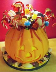 jack o lantern cake (except  less candy on top because there's too much going on up there instead do just a few recognizable treats like the black and orange wrapped peanut butter candies, and candy corn, lollipops etc)