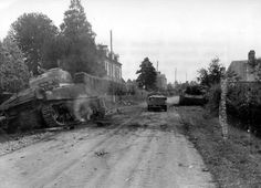 A 'Stug SS - 1 Sturmgeschütz - Abteilung' of the 'LSSAH' destroyed on the road from Avranches ( D5 ) in Juvigny-le-Tertre . A Sherman of the US 32nd Armored Regiment is also left smouldering.