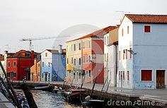 Photo taken on the island of Burano in the village of fishermen and lace embroiderers in the municipality of Venice Italy. In the picture you see, in the foreground, a canal with boats moored on both banks. On the opposite bank, illuminated by the setting sun, the different colored houses are lined up. Above the roofs of the blue sky very tenuous.