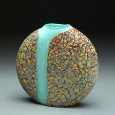 Cascade Vase with Opal Blue Interior by Thomas Spake. This flattened blown glass vase was created by layering opaque sand, tan, brown, and red glass frits and powders to create the intricate pattern. The frit and powders are laid out in a specific format on a steel plate. Once the glass is on the blow pipe, the pattern is rolled up onto the piece and melted into the surface of the glass. After the vase is cooled, the waterfall effect is created by using a diamond wheel that spins on a lathe…