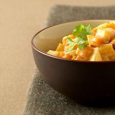 Schil de aardappels. Schil de mango en snij het vruchtvlees van de pit. Snij aardappels en mango in blokjes van 2 x 2 cm. Was de lente-uitjes en snij ze fijn. Pel de knoflook. Verhit de olie in een wok. Voeg aardappels, lente-ui en currypasta toe. Pers er de knoflook boven uit en schep goed om. Bak al omscheppend op een hoog vuur ca. 2 minuten. Voeg de kokosmelk toe, breng aan de kook en laat onder af en toe roeren ca. 15 minuten zachtjes koken. Voeg de mangoblokjes toe en warm alles nog 2…