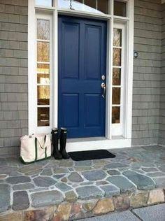 Dark blue door on a grey house with white trim.