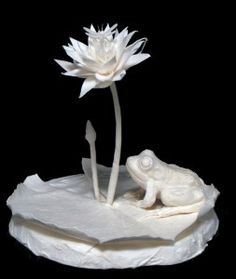 Cast paper sculpture by Patty Eckman of frog waiting for a dragonfly to come off the Lily flower.