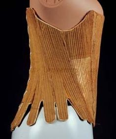 "Stays, right side view Kent State University Museum  Object Number	1983.001.2481 Object Name	Corset Date	1700-1799 Culture	American Description	Yellow cotton stays, Baleine boned, leather inside tabs, corset.  No original catalog card exists.  ""Beige boned stays with waist tabs. European or American, ca. 1770-1790. Quilted cotton, tan leather binding at underarms, baleen boning."" (Age of Nudity label copy, 2006)"