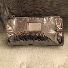 Michael Kors Metallic Sliver Cosmetics Case Michael Kors Metallic Sliver Cosmetics Case. Never used. Two slip pockets on the inside. Color is a sliver/gunmetal. MICHAEL Michael Kors Bags Cosmetic Bags & Cases