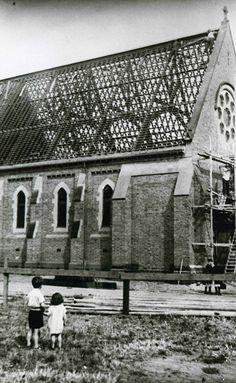 Two children looking at construction work being undertaken on St Thomas' Church of England in Essendon  around 1932.