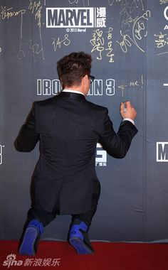 """Robert Downey Jr. signs an autograph wall (as """"Me!"""") in Beijing, China during the red-carpet Chinese premiere of """"Iron Man 3"""" (April 2013)."""