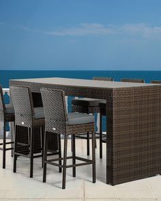 The Pier table and 6 bar stool patio bar set offers an inimitable stylish design featuring a strong black wicker construction and thick green cushions for added comfort and support.
