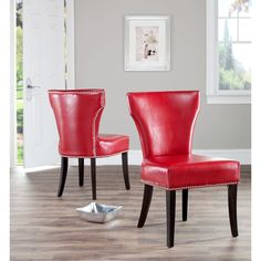 Update the look of your dining room with this set of two bicast leather dining chairs. The nail trim of the red faux-leather chairs will add a look of distinction to your dining room, and concave curved backs and deep seats provide comfort.