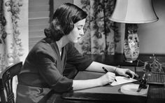 Portrait of woman writing letter at desk