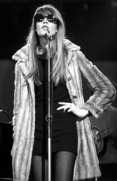 French singer Francoise Hardy wearing sunglasses and a long fur coat during a performance, circa 1965. (Photo by Andrew Maclear/Hulton Archive/Getty Images)