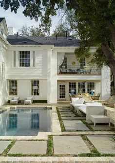 Beautiful white home with spacious backyard and swimming pool