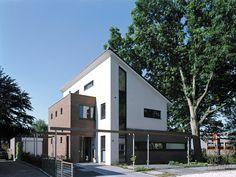 Dit huis met zijn moderne uitstraling is ingepast in een bestaande omgeving. De gevels zijn wit gestuukt en de aanbouwen zijn gemetseld met een bruine baksteen.