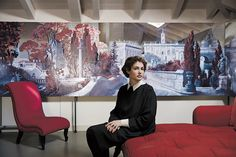 """Elkann in a Valentino dress seated in her studio in front of the American artist Rachel Feinstein's painting """"Panorama of Rome 2012."""""""