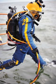 Diver jumping into the water wearing a Mark 12 outer garment