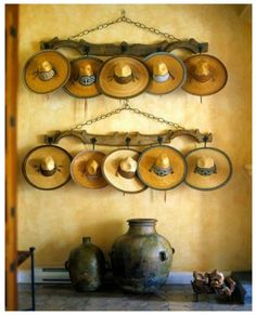 Mexican Sombreros- I would so just collect these for no reason!!  Using antique wood farm animal yokes to display them is inspired.