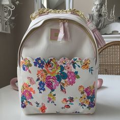 Betsey Floral Scallop Studded Backpack Beautiful unusual backpack with front scalloped studded pocket. Gold chain top handle & detachable Tassel key chain. Inside back has zip pocket & 2 open pockets. Opposite side also has 2 pockets. New Betsey Johnson Bags