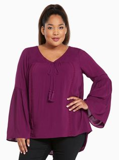 A peasant top that's perfectly groovy in a purple haze challis top is recalling the 70's with bell sleeves crochet detailing the front and a tassel tie neck $44.90