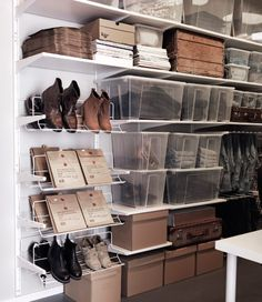 Storage room with white shelves, shoe organizers, cardboard and transparent boxes