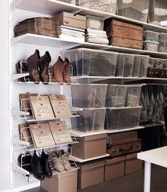 Espaço de arrumação com prateleiras brancas, sapateiras, caixas de cartão e transparentes.