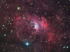 The Bubble Nebula. Although it looks delicate, the 10 light-year diameter bubble offers evidence of violent processes at work. Above and right of the Bubble's center is a hot, O-type star, several 100,000 times more luminous and approximately 45 times more massive than the Sun. A fierce stellar wind and intense radiation from that star has blasted out the structure of glowing gas against denser material in a surrounding molecular cloud.