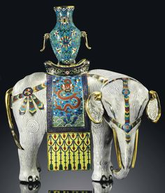 A LARGE CLOISONNÉ ENAMEL CAPARISONED ELEPHANT  JIAQING PERIOD (1796-1820)  The white elephant is magnificently modelled standing foursquare, with its head turned slightly to one side, supporting a twin-handled vase on its back on top of the saddle. Its saddle cloth is decorated with dragons, and its multi-coloured trappings are detailed with floral designs.