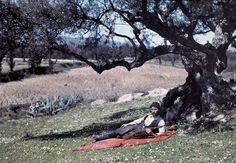 A hunter lies under an olive tree on the island of Crete;  1920's; Images by Maynard Owen Williams / Wilhelm Tobien  Source: National Geographic Stock