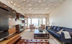 faux plafond design en blanc neige, suspensions originales, canapé bleu, table basse et méridienne en cuir marron