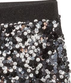 Sequined skirt in mesh with an elasticized waistband and jersey lining.