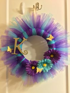Made this tulle wreath for my niece. Materials: 12in foam wreath, one roll each of purple tulle and turquoise blue tulle (one roll=6in wide 20yds long), one roll of glitter purple tulle (6in wide 10yds long), block letter K spray painted in champagne color, clip on flowers and butterflies and gold ribbon to hang. All materials except for gold ribbon were purchased at Michael's for $27 with a 20% coupon!